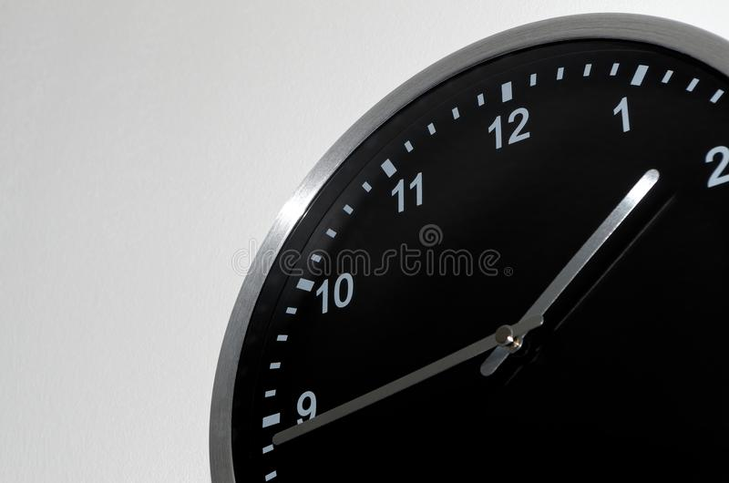Quarter to two setting on the black wall clock. Black wall clock ion white background with a quarter to two setting stock photography