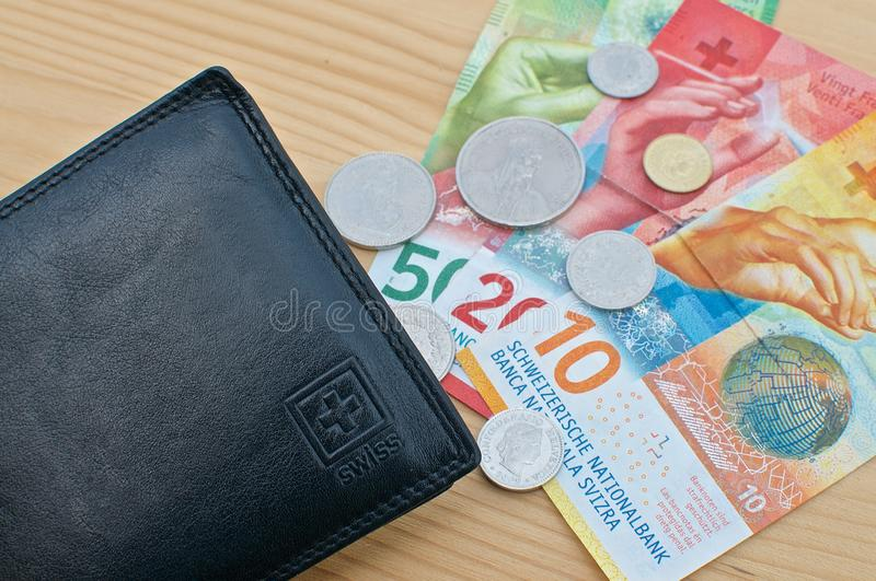 Black wallet and Swiss currency stock image
