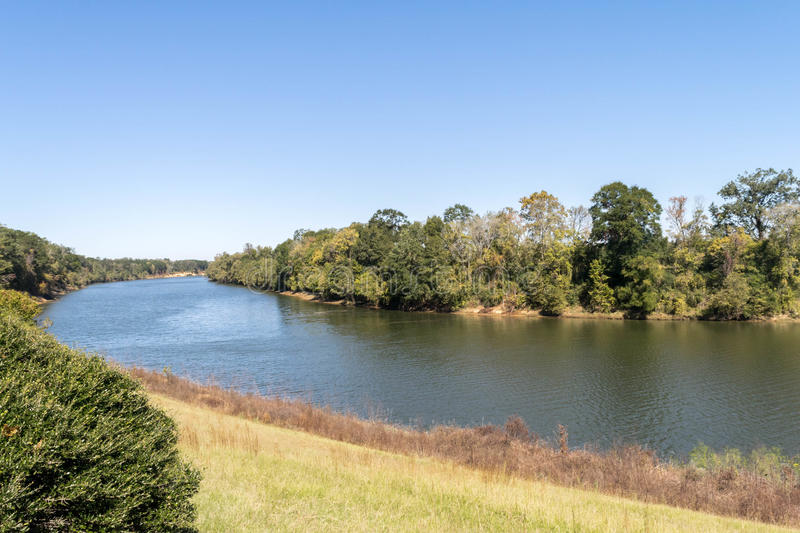 Black Warrior River near Moundville, Alabama, USA. River bend in distance, surrounded by trees on cloudless day in autumn royalty free stock photos
