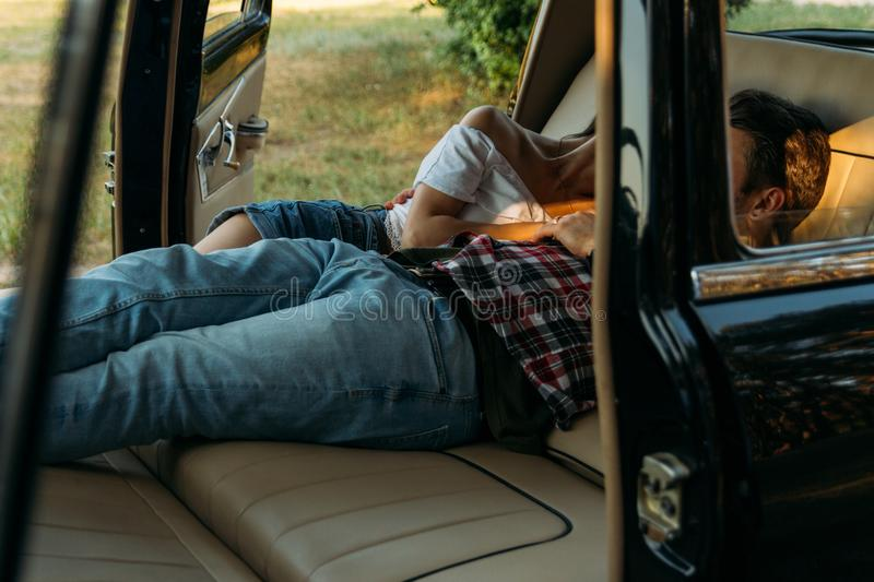 Date in the car.people who are lying in the car and holding hands. look through the window in the car.side view.black watch on man. Black watch on man& x27;s stock images