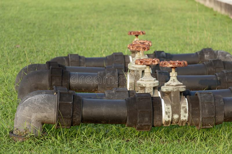 Black water pipes joined with rusty red valves for safety and clean watering system in modern building construction and industrial. Black water pipes joined with royalty free stock image