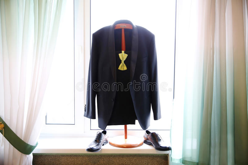 Black wedding suit with light green bow tie stock image