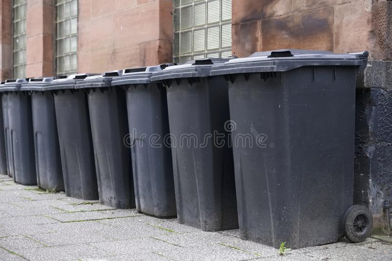 Black wheelie bins in a row on street with house numbers printed on front waiting for bin men to collect royalty free stock photos