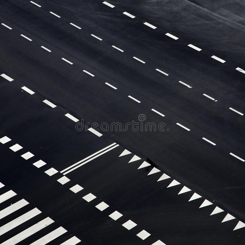 Black and white abstract. Angled abstract of black asphalt with white lines and shaped markings, from an aerial viewpoint stock photography