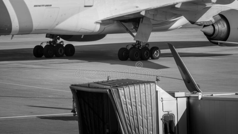 Black and white abstract image of airplane chassis, telescopic boarding gate and airport runway. Black and white abstract image of airplane chassis, telescopic royalty free stock photos