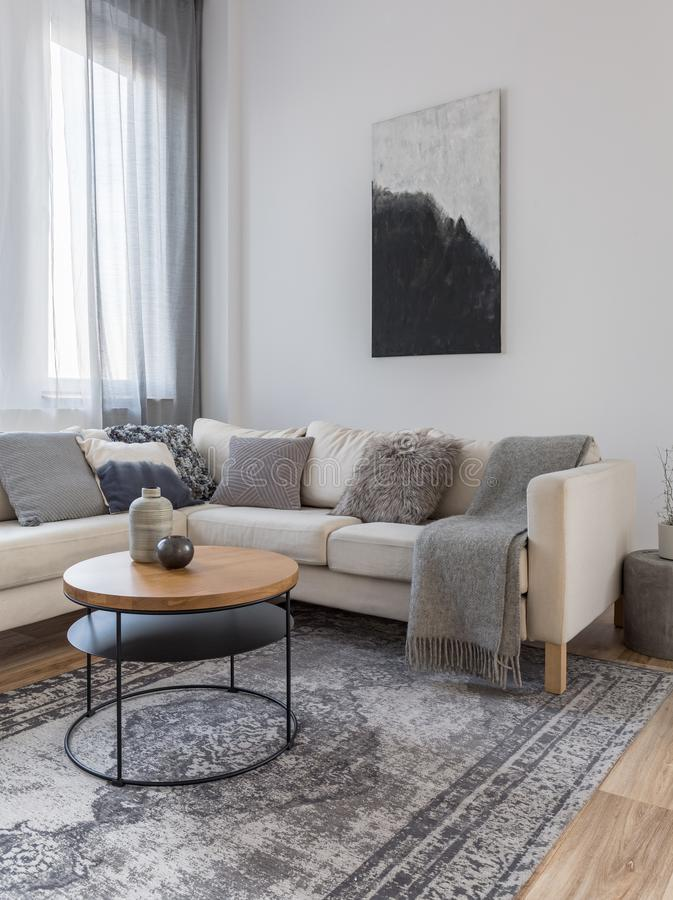 Black and white abstract painting on white empty wall of chic living room interior with corner sofa stock image
