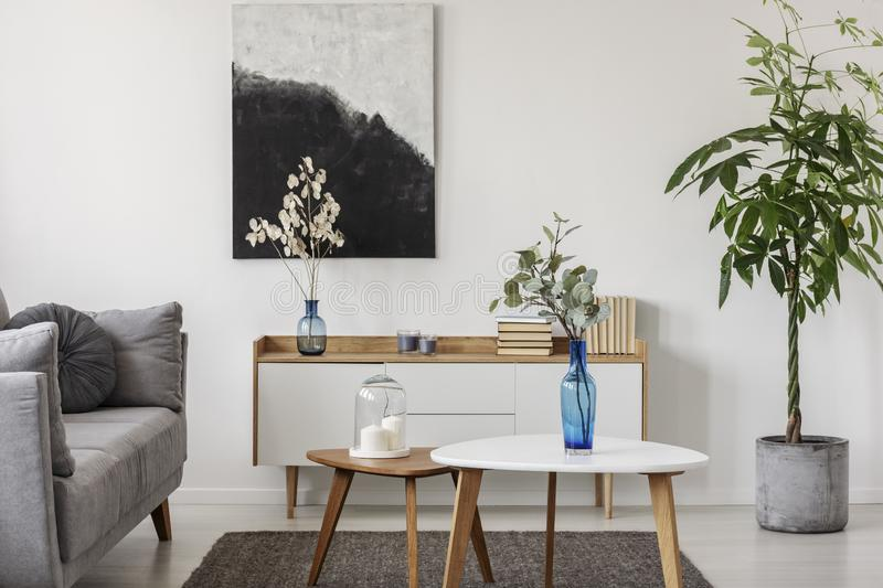 Black and white abstract painting on empty wall of cozy living room interior stock image