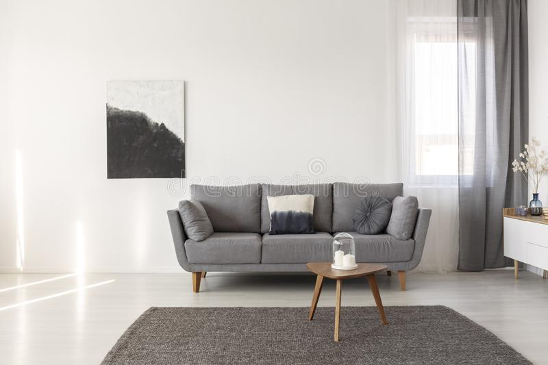 Black and white abstract painting on empty wall of cozy living room interior stock photo