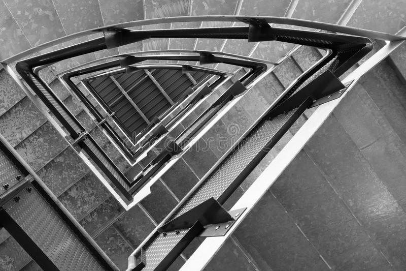 Black and white abstract of repeating patterns in stairwell. An abstract image of a stairwell from the bottom looking up, showing contrasts of light and shade stock photo