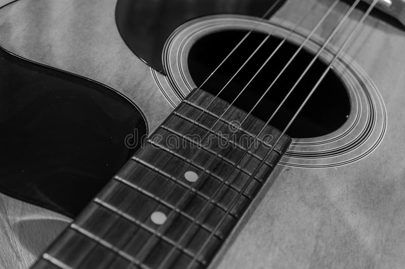 Black and white acoustic guitar with sound hole and pickguard. Close royalty free stock photos