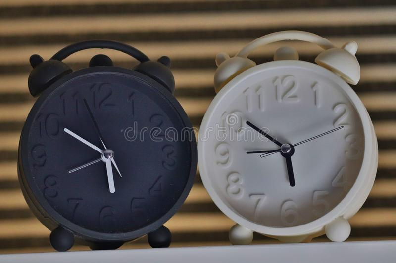 Black and white alarm clocks. Placed at shelve at home stock photos