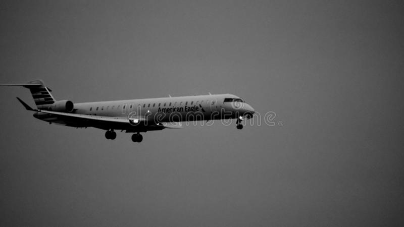 Black and white American Airlines Bombardier airplane coming in for a landing. stock images