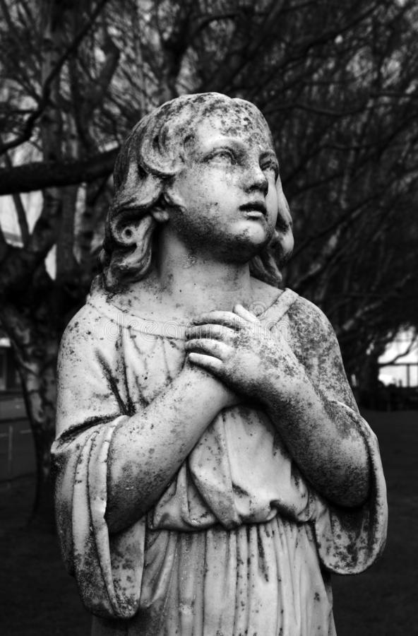 Black and White Angel Sculpture in Churchyard Cemetery stock images