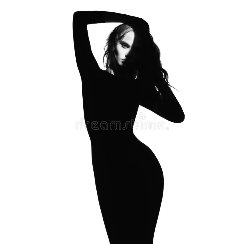 Black and white fashion portrait of beautiful lady. Black and white art fashion portrait of beautiful woman with a beam of light on her face. Model posing on stock images