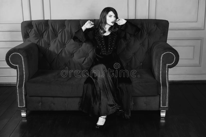 Black and white art monochrome photography. Beautiful girl with long hair and natural make-up and pale skin. A woman in a black retro dress sitting on a couch stock images