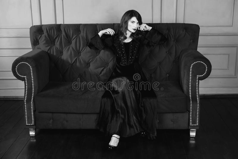 Black and white art monochrome photography. Beautiful girl with long hair and natural make-up and pale skin. A woman in a black retro dress sitting on a couch stock photo