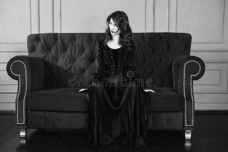 Black and white art monochrome photography. Beautiful girl with long hair and natural make-up and pale skin. A woman in a black retro dress sitting on a couch royalty free stock photography