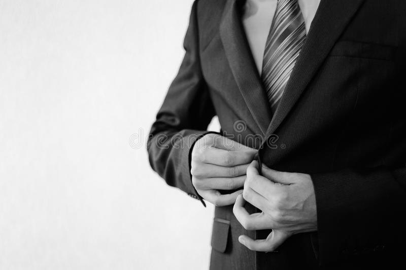 Man in a classic black suit with a butanier standing at the window. Black and white art photography monochrome, man buttoning his waistcoat on. Men`s style stock images