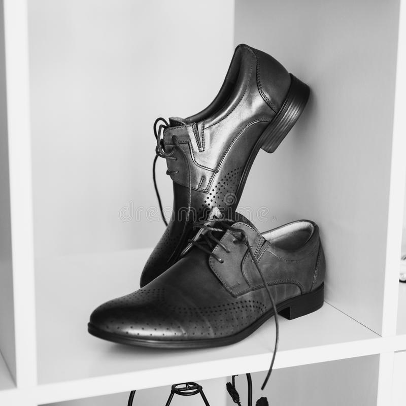 Man`s shoes stand on a shelf. Black and white art photography monochrome, man`s shoes stand on a shelf. Men`s style, fashion. Charges groom royalty free stock image