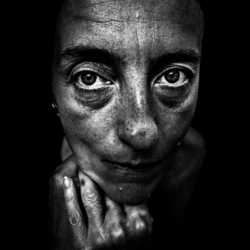 Black and white artistic portrait of a sad woman. Looking straight into the camera with added film grain royalty free stock photo
