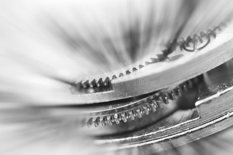 Black and white background. Metal Cogwheels in clock mechanism. Macro stock images