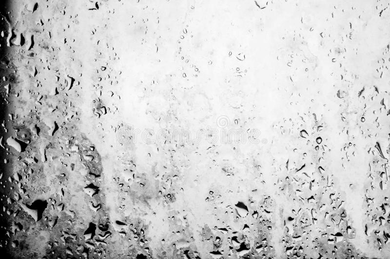 Black and White Background Water drops on the dirty window glass stain stock photo
