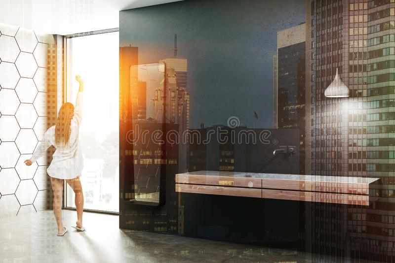 Black and white bathroom, double sink, woman. Woman in modern bathroom with black and gray honeycomb pattern walls, concrete floor and white double bathroom sink royalty free stock image