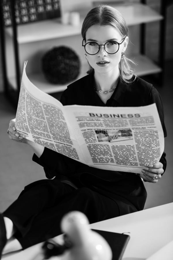 Black and white of beautiful businesswoman in black clothes and shoes sitting at table and. Holding newspaper royalty free stock image