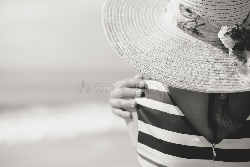 Black and white of beautiful romantic lady enjoying summer beach looking at sea. Back view royalty free stock photo