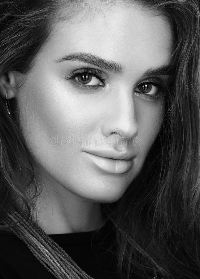 Black and white beauty closeup portrait of beautiful young woman with wet hair and professional makeup stock photo