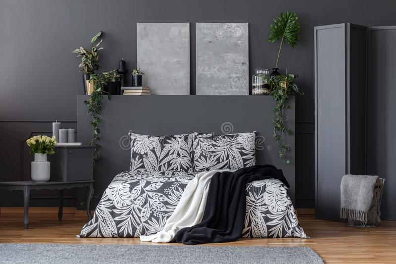 Black and white bedclothes. Black and white floral bedclothes on bed with two blankets standing in dark room interior with simple paintings and fresh plants stock images