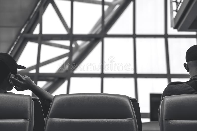 Black and white behind image of a man sitting and waiting for depart while another man talking on a phone royalty free stock images
