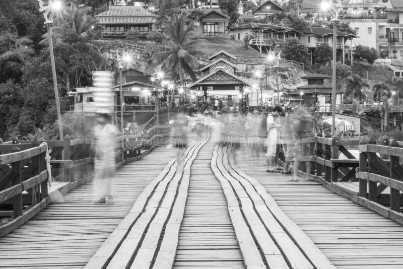 Black and white blur image of Traveler crossing bamboo bridge or Mon Bridge in Sangklaburi. Kanchanaburi, Thailand. stock image