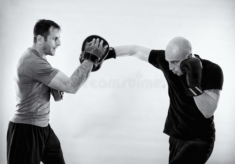 Black and white of boxer with trainer. Boxer and his coach hitting mitts, black and white image royalty free stock images