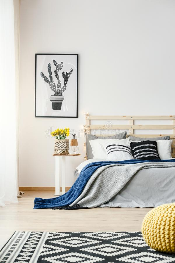 Black and white cactus poster hanging on the wall in bright bedroom interior with yellow fresh flowers, double bed and patterned stock photos