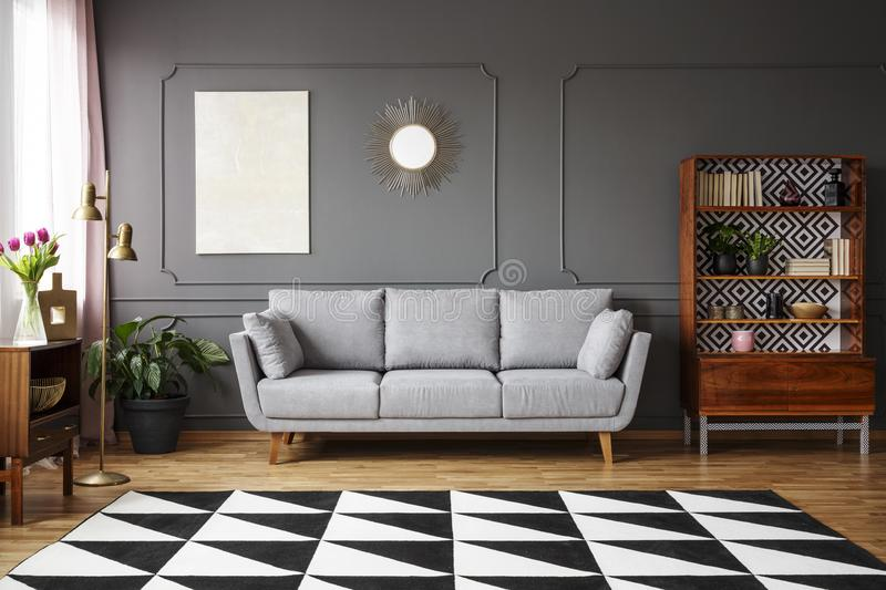 Black and white carpet with geometric pattern placed on the floor in dark living room interior with grey couch, vintage cupboard stock images