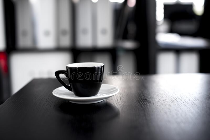 Black and White Ceramic Tea Cup With Saucer on Black Wooden Table stock photos