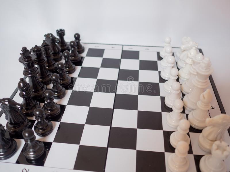 Black and white chess-Army are standing on a board with white background, challenges planning business strategy to success concept royalty free stock image