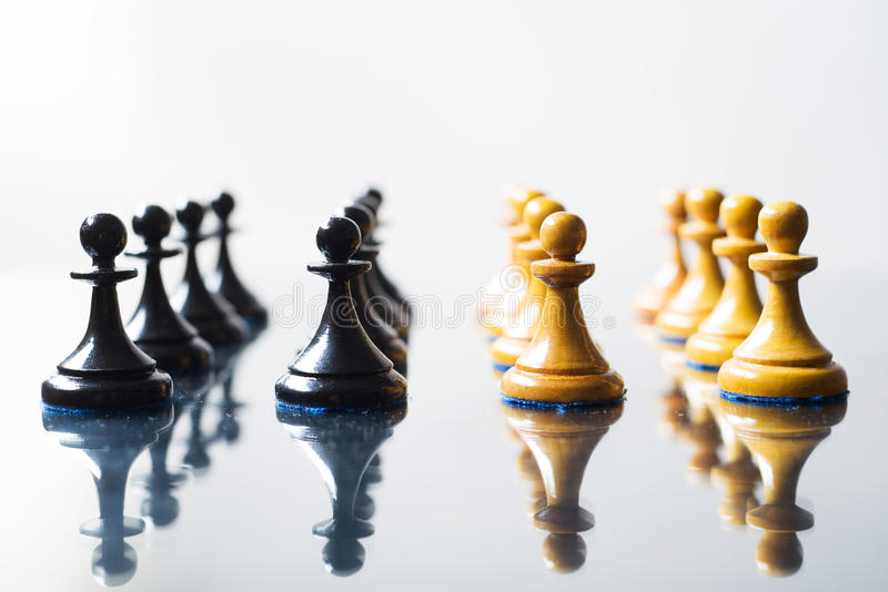 Black and white chess pawns. On white royalty free stock images
