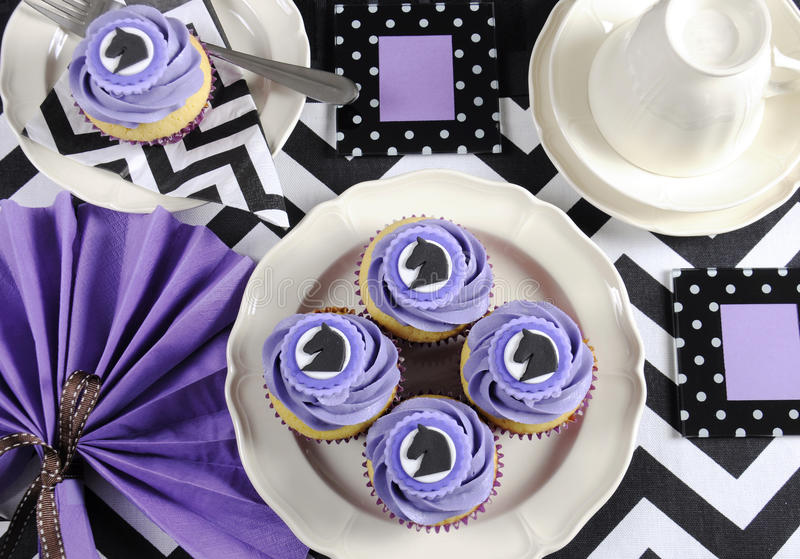 Black and white chevron with purple theme party table with cupcakes. royalty free stock photography