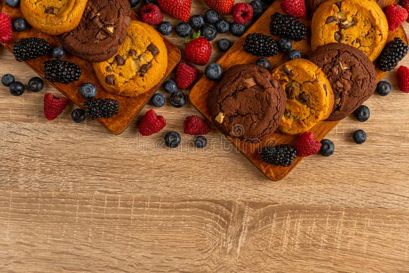 Black and white chocolate cookies with forest fruits with copyspace below stock images