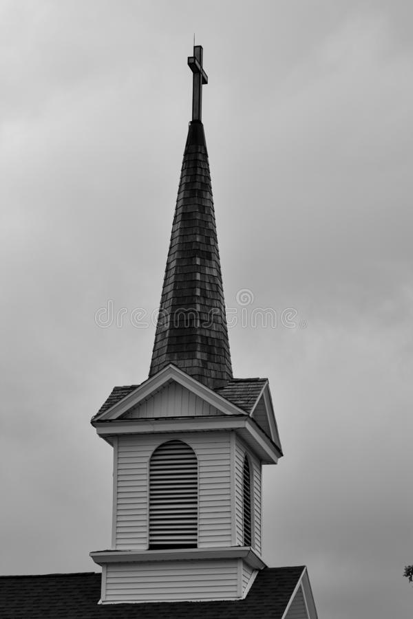 Black and white of a Christian Church steeple with a cross at the top stock photo