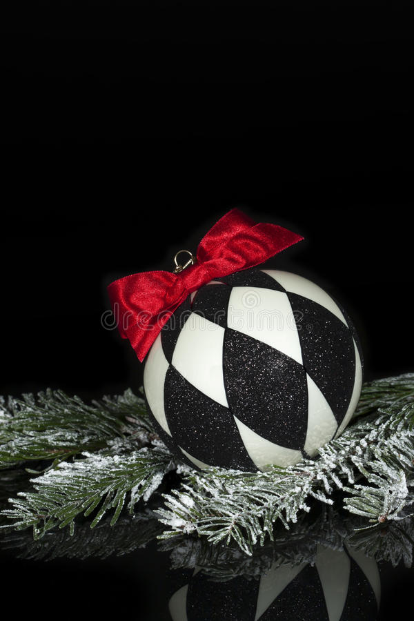 Black White Christmas Ornament 2. A Christmas ornament with black and white diamond pattern and red bow resting on snow covered evergreen bough on black royalty free stock photos