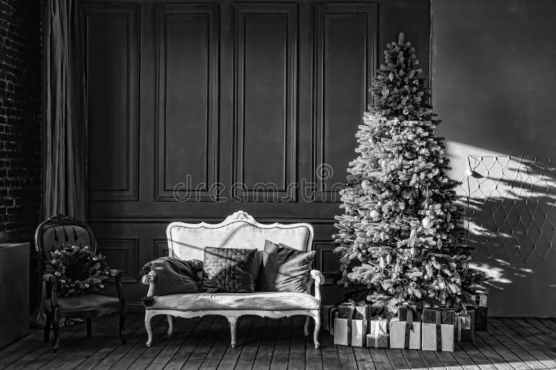 Black and white, Christmas tree in royal interior. New Year`s Living Room with antique stylish white sofa with luxurious golden royalty free stock image