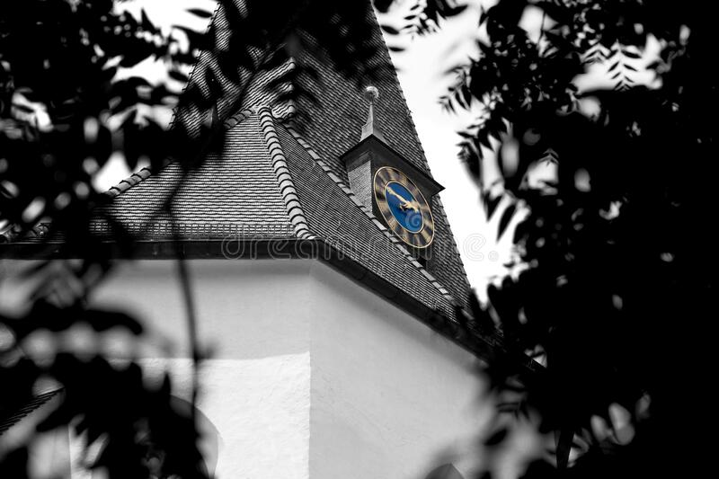 Black and white church with tiled roof between trees and leaves with visible church tower and blue dial, clock with speed effect,. Time passes quickly, by stock photo