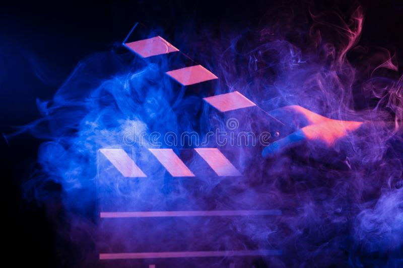 Black and white clapperboard for cinema close up among multicolored red and blue smoke in a man's hand giving a command to start. Shooting on a black stock image