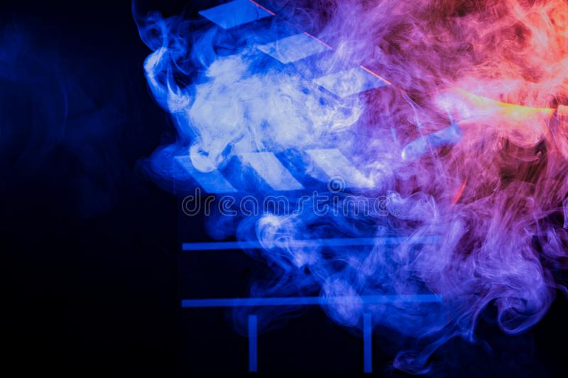 Black and white clapperboard for cinema close up among multicolored red and blue smoke in a man's hand giving a command to start. Shooting on a black royalty free stock images