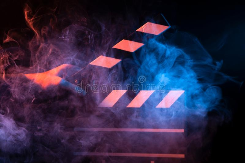 Black and white clapperboard for cinema close up among multicolored red and blue smoke in a man's hand giving a command to start. Shooting on a black royalty free stock image