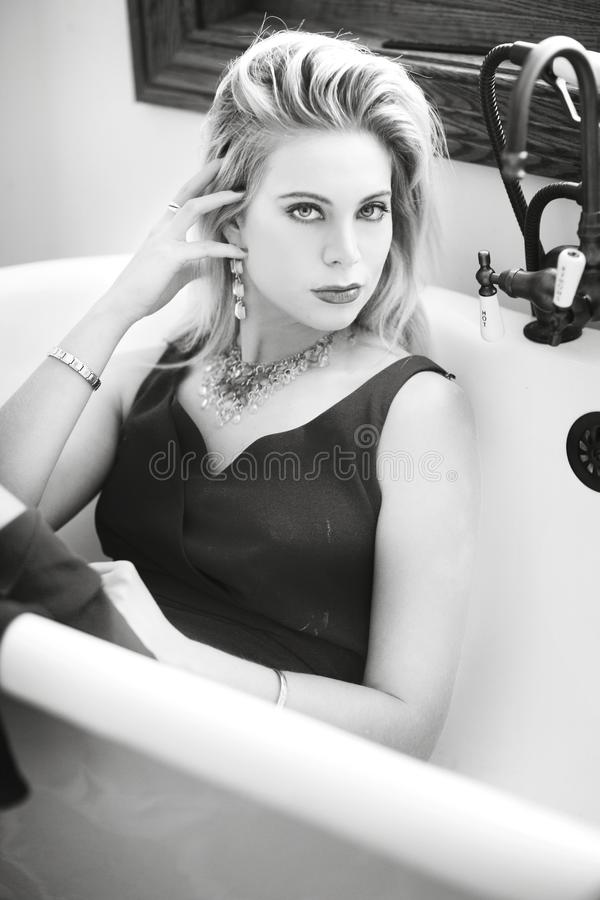 Black and white close up of a blond woman in a vintage tub with a black dress. stock images