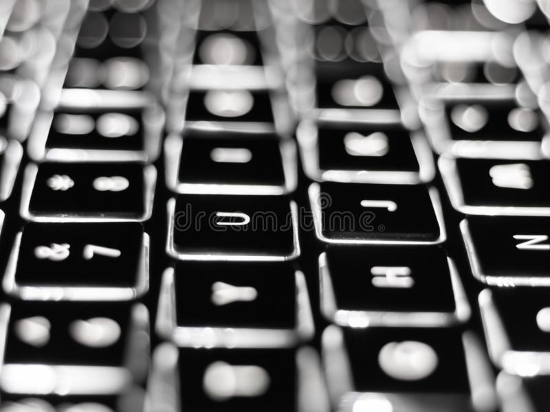 Black and white close-up on illuminated keys of computer keyboard royalty free stock photography